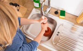 woman trying to unclog sink with plunger